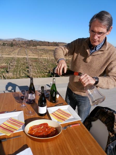Philippe Modat sur le toit de sa cave en plein caraffage de son vin pour accompagner la cuisine catalane de sa maman. Photo©MichelSmith