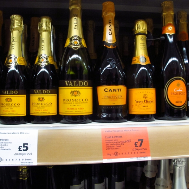 UK supermarket shelf with an array of yellow/gold/orange labelled Prosecco