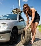 Young, confident woman, changing a flat tire on her car on a rural road with a wind mill in the backgrounc